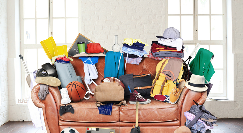 Sofa covered in clutter.